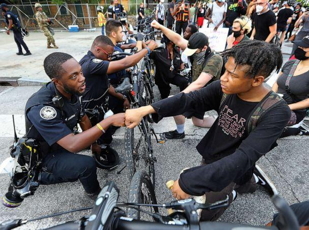PHOTO: Atlanta Police Officer J. Coleman and protester Elijah Raffington fist bump in a symbolic gesture of solidarity outside the CNN Center at Olympic Park, in Atlanta, June 3, 2020. (Curtis Compton/Atlanta Journal-Constitution via AP)