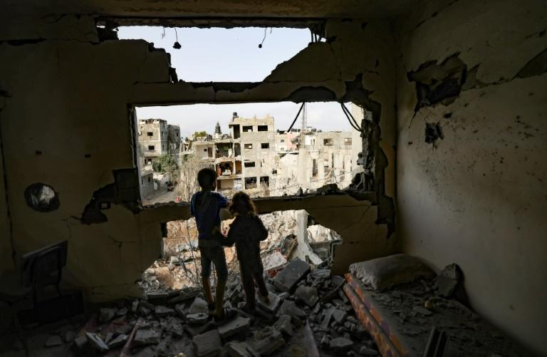 Palestinian children look out from a home damaged by Israeli bombardment in Gaza City