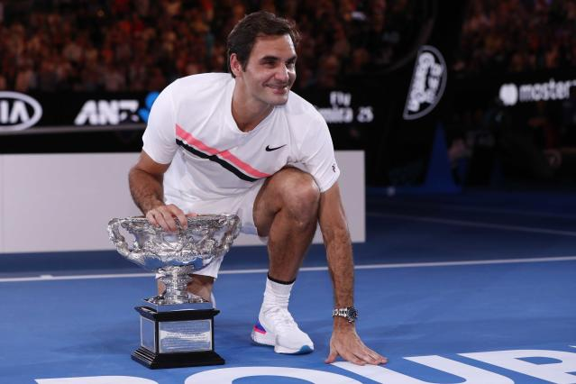 Tennis - Australian Open - Men's singles final - Rod Laver Arena, Melbourne, Australia, January 28, 2018. Switzerland's Roger Federer celebrates with the trophy as he poses after winning the final against Croatia's Marin Cilic. REUTERS/Issei Kato