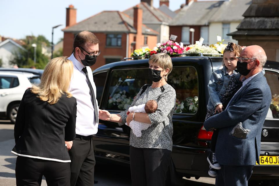 Husband Josh with his newborn daughter Eviegrace, being carried by a relative (name not known) after the coffin of Samantha Willis (nee Curran) from Strathfoyle is taken from St Columb's Church, Londonderry, following her funeral. The mother-of-four died with Covid-19 shortly after giving birth on Friday. Picture date: Monday August 23, 2021.