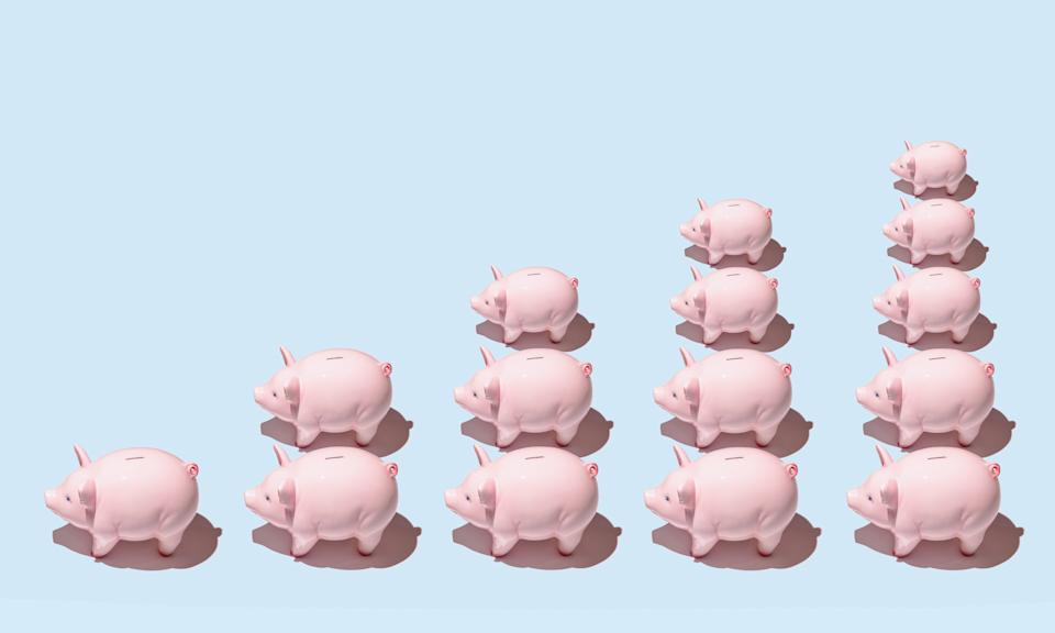 Differently sized pink ceramic piggy banks in stacks forming a bar graph on blue surface