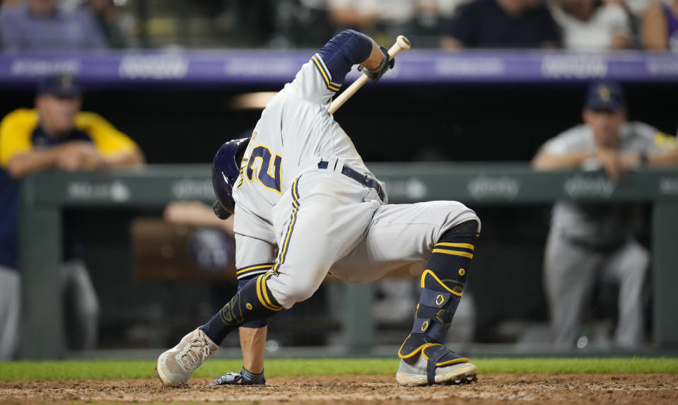 Milwaukee Brewers' Luis Urias avoids a high, inside pitch from Colorado Rockies reliever Yency Almonte during the seventh inning of a baseball game Saturday, June 19, 2021, in Denver. (AP Photo/David Zalubowski)