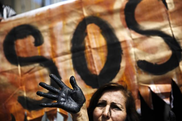 <p>An activist with her hand painted black to symbolize the contamination of oil takes part in a protest performance demanding measures to prevent oil spills, outside the national oil company in Lima, Peru, Aug. 22, 2016. (Photo: Rodrigo Abd/AP) </p>