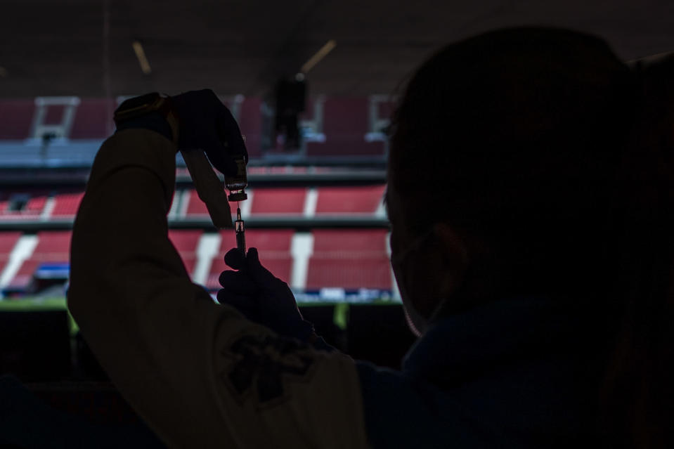 A health worker holds a vial of the AstraZeneca vaccine to administer, during a mass vaccination campaign at Wanda Metropolitano stadium in Madrid, Spain, Wednesday, March 24, 2021. Spain resumed the use of the AstraZeneca vaccine on Wednesday by extending it to adults up to 65 years old. (AP Photo/Manu Fernandez)