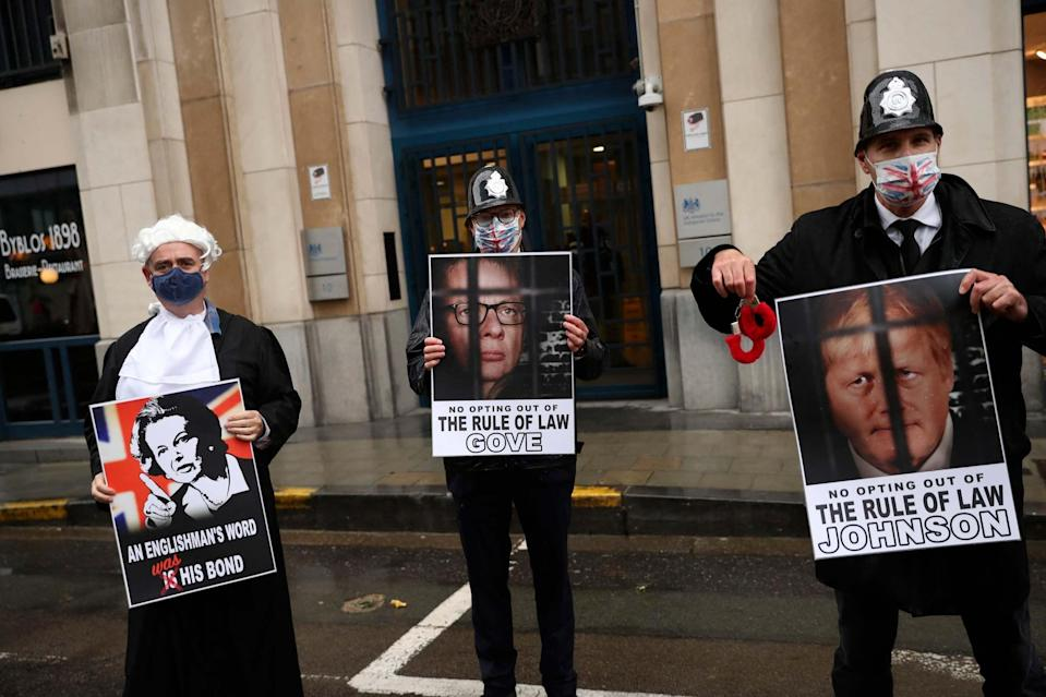 Anti Brexit protesters hold signs after the Chancellor of the Duchy of Lancaster Michael Gove left the third meeting of the EU-UK Joint Committee outside the UK representation in Brussels, Monday (AP)