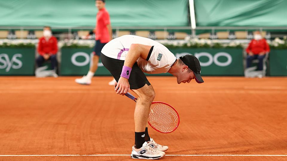 Dominik Koepfer, pictured here spitting on the court during his French Open clash with Roger Federer.