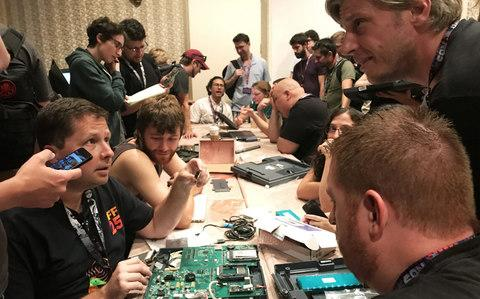 "People pull apart computers used in voting machines in a bid to uncover security bugs during a ""hacker voting village"" exercise at the Def Con hacking conference in Las Vegas - Credit: Reuters"