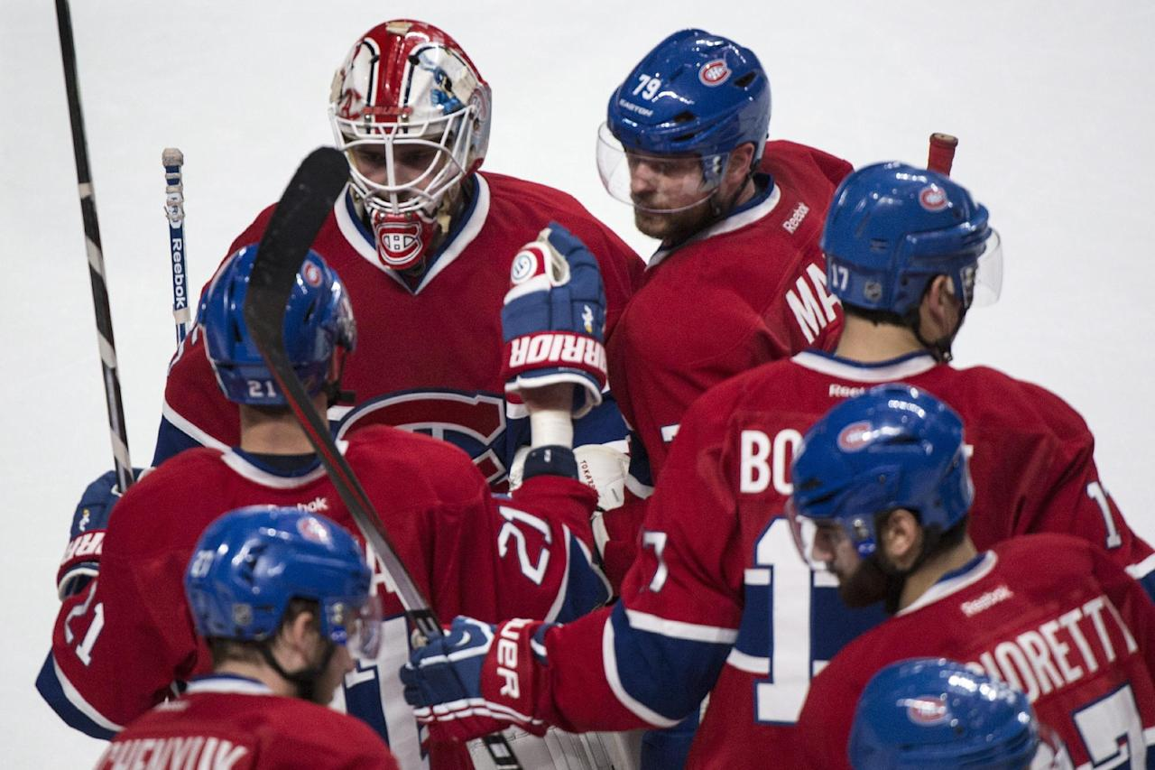 Members of the Montreal Canadiens gather around goalie Dustin Tokarski to celebrate their 7-4 victory over the New York Rangers in Game 5 of the NHL hockey Stanley Cup playoffs Eastern Conference finals, Tuesday, May 27, 2014, in Montreal. (AP Photo/The Canadian Press, Paul Chiasson)