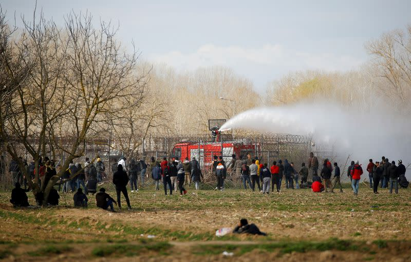A Greek fire fighter uses a water cannon as migrants look on near Turkey's Pazarkule border crossing with Greece's Kastanies, near Edirne