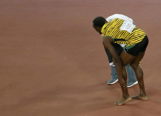 Winner Bolt of Jamaica rubs his foot after being hit by a cameraman on a Segway (not pictured) after competing at the men's 200 metres final during the 15th IAAF World Championships at the National Stadium in Beijing