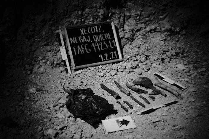 Human remains are lined up along a blackboard which identifies the site where human remains were found. Xecotz, Nebaj, Quiche, Guatemala. February 9, 2021.
