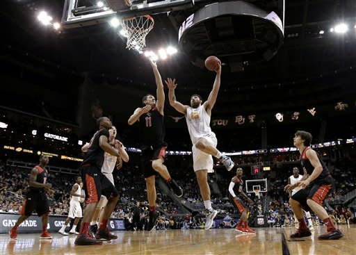 West Virginia forward Deniz Kilicli (13) puts up shot past Texas Tech forward Dejan Kravic (11) during the first half an NCAA college basketball game in the Big 12 men's tournament Wednesday, March 13, 2013, in Kansas City, Mo. (AP Photo/Charlie Riedel)