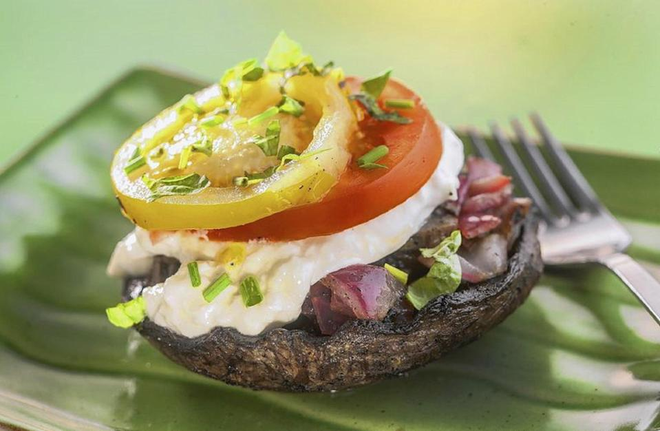 """<p>This stuffed, grilled mushroom is one of <a href=""""https://www.thedailymeal.com/entertain/ultimate-bbq-vegetarians-slideshow?referrer=yahoo&category=beauty_food&include_utm=1&utm_medium=referral&utm_source=yahoo&utm_campaign=feed"""" rel=""""nofollow noopener"""" target=""""_blank"""" data-ylk=""""slk:the best vegetarian dishes to serve at a cookout"""" class=""""link rapid-noclick-resp"""">the best vegetarian dishes to serve at a cookout</a>. Meat lovers and vegetarians alike will go nuts for these cheesy Portobello mushrooms.</p> <p><a href=""""https://www.thedailymeal.com/recipes/grilled-portobella-mushroom-burrata-recipe?referrer=yahoo&category=beauty_food&include_utm=1&utm_medium=referral&utm_source=yahoo&utm_campaign=feed"""" rel=""""nofollow noopener"""" target=""""_blank"""" data-ylk=""""slk:For the Lemon Grilled Portobellos With Burrata and Tomatoes recipe, click here."""" class=""""link rapid-noclick-resp"""">For the Lemon Grilled Portobellos With Burrata and Tomatoes recipe, click here.</a></p>"""