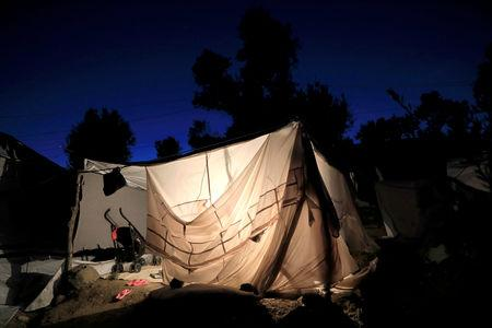 FILE PHOTO - A tent is illuminated at a makeshift camp next to the Moria camp for refugees and migrants on the island of Lesbos, Greece, September 18, 2018. Picture taken September 18, 2018. REUTERS/Giorgos Moutafis