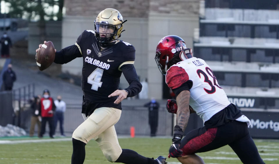 Colorado quarterback Sam Noyer, left, tries to get away from San Diego State linebacker Andrew Aleki during the first half of an NCAA college football game Saturday, Nov. 28, 2020, in Boulder, Colo. (AP Photo/David Zalubowski)