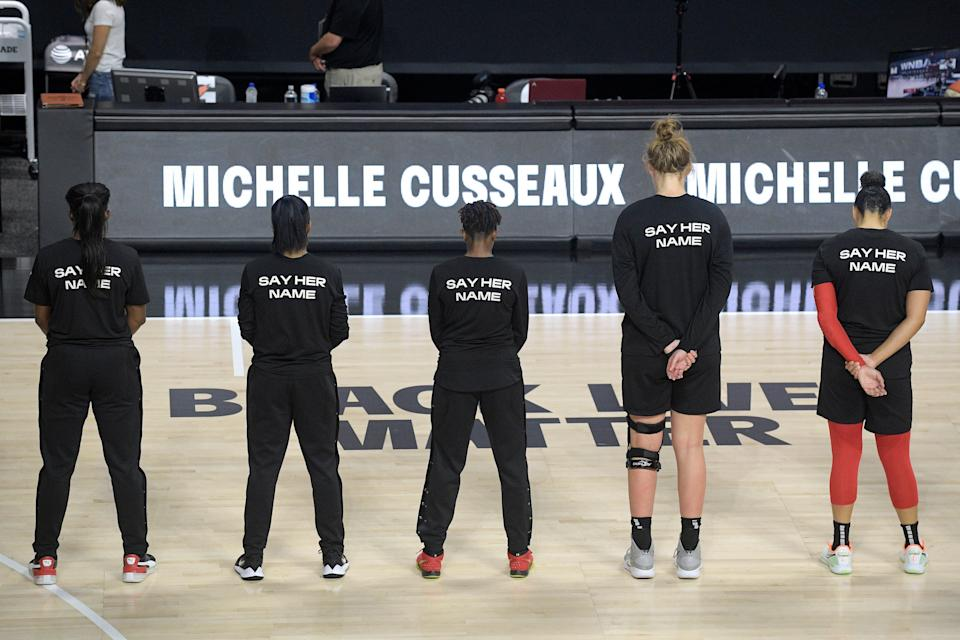 Members of the Las Vegas Aces honor Michelle Cusseaux with a moment of silence before a WNBA basketball game against the Washington Mystics, Aug. 15, 2020, in Bradenton, Fla.
