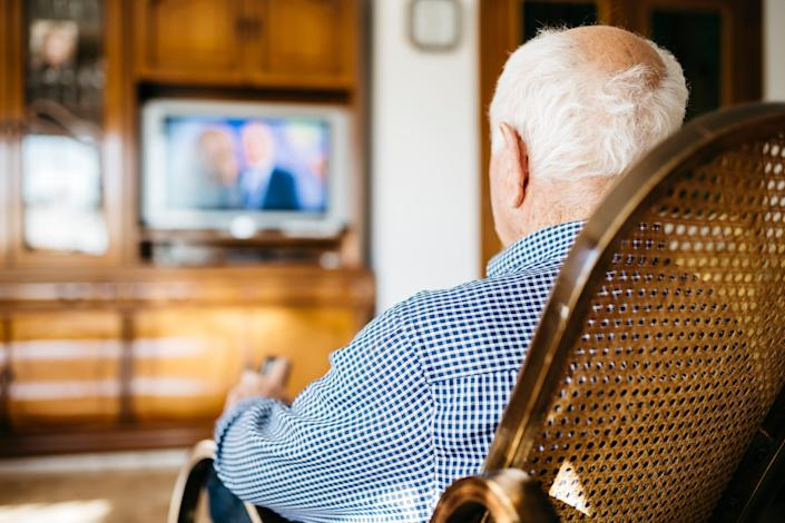 senior woman watching tv at home
