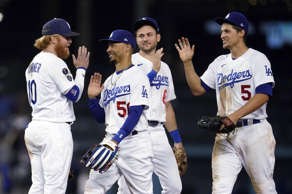 Los Angeles Dodgers' Justin Turner, Mookie Betts, Trea Turner and Corey Seager, from left, celebrate the team's 8-4 win over the Arizona Diamondbacks in a baseball game Tuesday, Sept. 14, 2021, in Los Angeles. (AP Photo/Marcio Jose Sanchez)