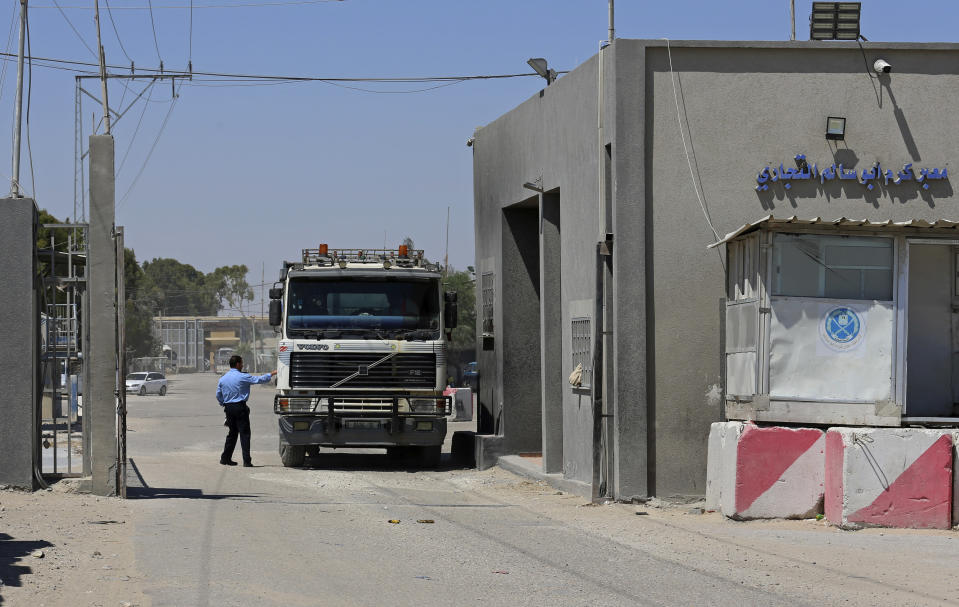A Hamas security officer checks a truck entering Gaza at the gate of the Kerem Shalom cargo crossing with Israel, in Rafah, southern Gaza Strip, Monday, June 21, 2021. Israel on Monday eased some restrictions on the Gaza Strip that have threatened a fragile cease-fire which halted an 11-day war last month with the territory's Hamas rulers, Palestinian officials said. (AP Photo/Adel Hana)