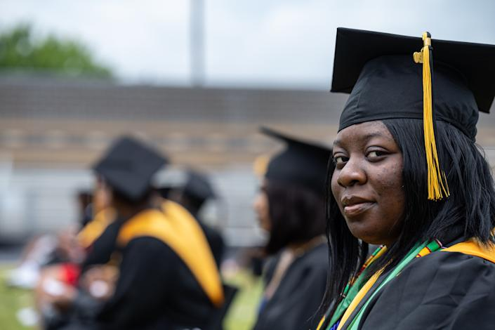 LOUISVILLE, KY - MAY 28: A former student of Jefferson County Public Schools grins and looks to the side while in cap and gown during a makeup graduation ceremony at Central High School on May 28, 2021 in Louisville, Kentucky. The makeup ceremony was held to celebrate the students whose graduations were disrupted due the coronavirus pandemic the previous year. (Photo by Jon Cherry/Getty Images)