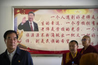 Monks and Chinese government officials stand near a billboard depicting Chinese President Xi Jinping at the Tibetan Buddhist College near Lhasa in western China's Tibet Autonomous Region, as seen during a rare government-led tour of the region for foreign journalists, Monday, May 31, 2021. Long defined by its Buddhist culture, Tibet is facing a push for assimilation and political orthodoxy under China's ruling Communist Party. (AP Photo/Mark Schiefelbein)