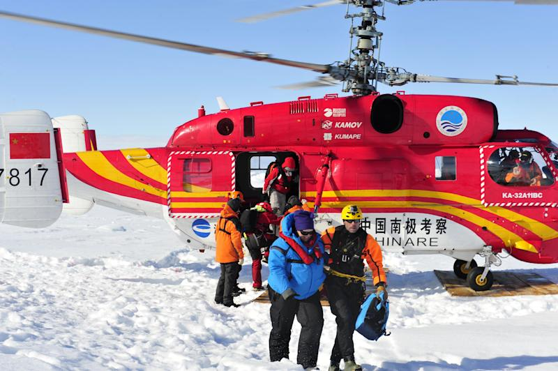 In this photo provided China's official Xinhnua News Agency, the first group of passengers of the trapped Russian ship MV Akademik Shokalskiy arrive at a safe surface off the Antarctic Thursday, Jan. 2, 2014. A helicopter rescued all 52 passengers from the research ship that has been trapped in Antarctic ice, 1,500 nautical miles south of Hobart, Australia, since Christmas Eve after weather conditions finally cleared enough for the operation Thursday. (AP Photo/Xinhua, Zhang Jiansong) NO SALES
