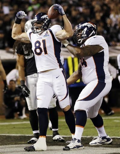 Denver Broncos tight end Joel Dreessen (81) reacts after scoring a touchdown on a 6-yard pass from quarterback Peyton Manning during the first quarter of an NFL football game against the Oakland Raiders in Oakland, Calif., Thursday, Dec. 6, 2012. At right is Broncos tackle Orlando Franklin. (AP Photo/Marcio Jose Sanchez)