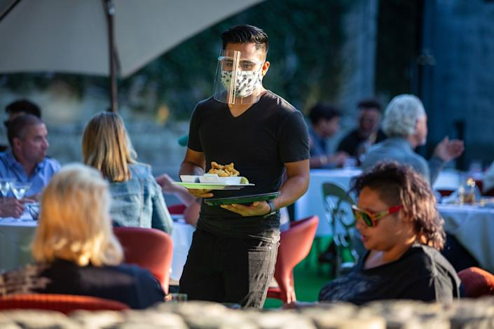 """Customers dine on the outdoor patio at La Boheme in West Hollywood in July, 2020. <span class=""""copyright"""">(Jason Armond / Los Angeles Times)</span>"""