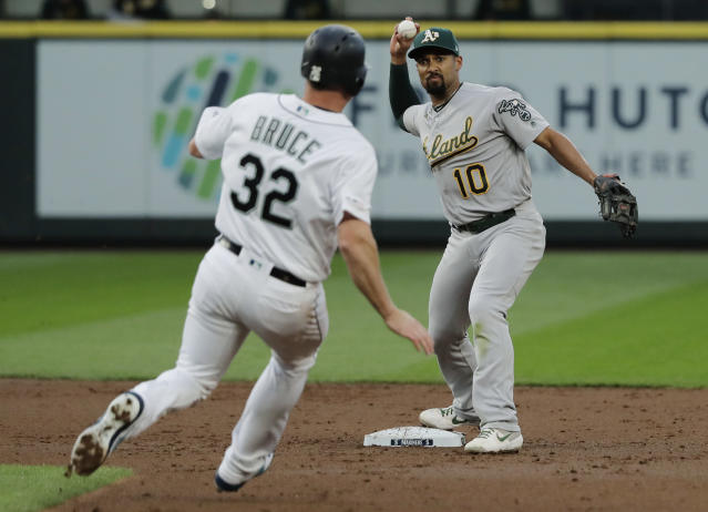 Oakland Athletics shortstop Marcus Semien (10) throws to first to get out Seattle Mariners' Shed Long (not shown) for the double play after forcing Seattle Mariners' Jay Bruce (32) at second during the second inning of a baseball game, Monday, May 13, 2019, in Seattle. (AP Photo/Ted S. Warren)
