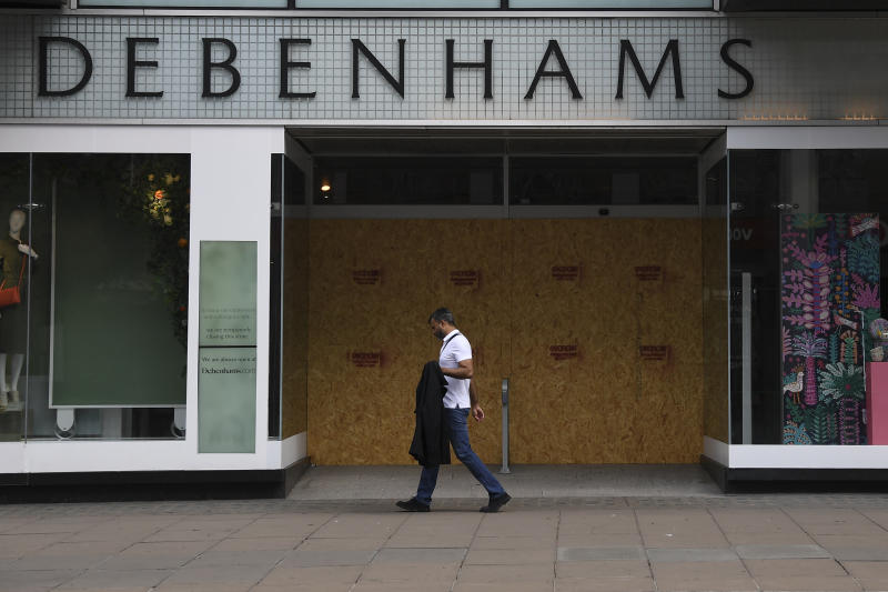 A man walks past a Debenhams store in the main shopping street Oxford Street, ahead of the reopening of the non-essential businesses on Monday, June 15, as some of the coronavirus lockdown measures are eased, in London, Friday, June 12, 2020. The British economy shrank by a colossal 20.4% in April, the first full month that the country was in its coronavirus lockdown, official figures showed Friday. (AP Photo/Alberto Pezzali)