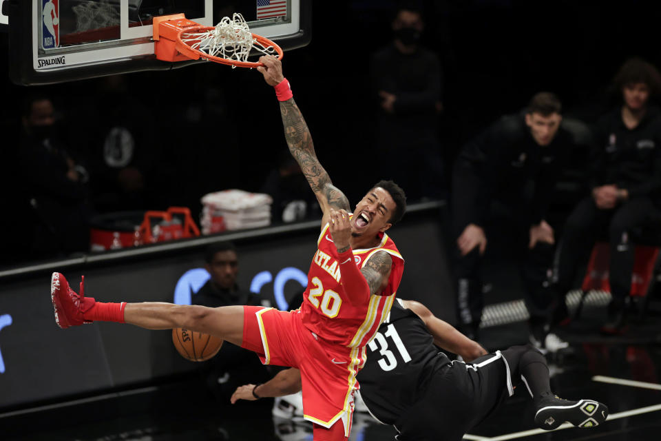 FILE - Atlanta Hawks forward John Collins (20) dunks next to Brooklyn Nets center Jarrett Allen during the second half of an NBA basketball game in New York, in this Friday, Jan. 1, 2021, file photo. Power forward John Collins, a key player in Atlanta's unexpected run to the Eastern Conference finals, has agreed to a five-year, $125 million contract to remain with the Hawks, a person with knowledge of the deal told The Associated Press on Wednesday, Aug. 4, 2021. (AP Photo/Adam Hunger, File)