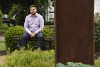 Brett Eagleson, son of Sept. 11 victim Bruce Eagleson sits in a memorial garden with a beam from the World Trade Center, Friday, July 2, 2021, at South Fire District in Middletown, Conn. Eagleson and others who lost family on Sept. 11 are seeking the release of FBI documents that allege Saudi Arabia's role in the terrorist attacks. A lawsuit that accuses Saudi Arabia of being complicit took a major step forward this year with the questioning under oath of former Saudi officials, but those depositions remain under seal and the U.S. has withheld a trove of other documents as too sensitive for disclosure. (AP Photo/Jessica Hill)