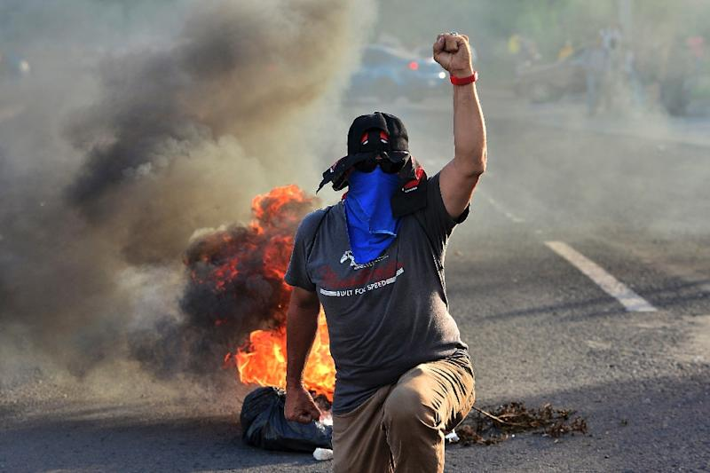 Honduran colleges students block a road in the capital Tegucigalpa during a protest against the government of President Juan Orlando Hernandez