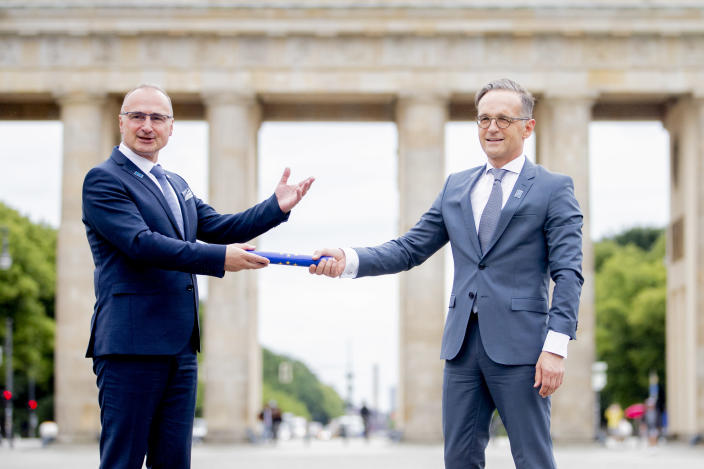 01 July 2020, Berlin: Gordan Grlic Radman (l), Foreign Minister of Croatia, symbolically hands over the baton to Heiko Maas, Foreign Minister, in front of the Brandenburg Gate as Germany takes over the EU Council Presidency from Croatia. Photo: Christoph Soeder/dpa picture alliance via Getty Images