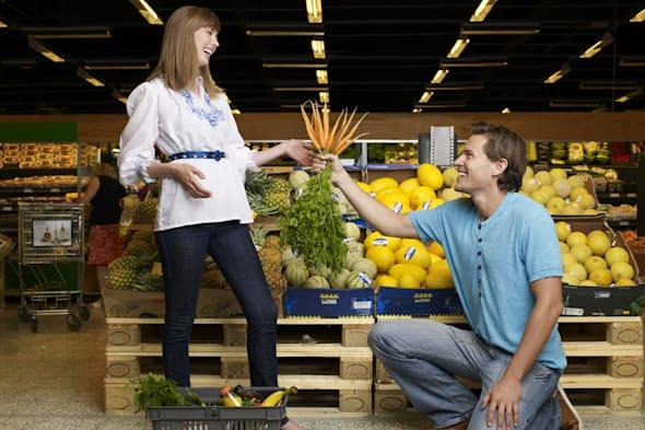Man propose with carrots in supermarket
