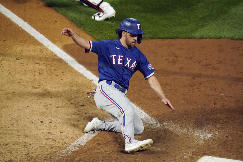 Texas Rangers' Charlie Culberson slides home to tie the score on a sacrifice fly ball by Isiah Kiner-Falefa in the ninth inning of a baseball game, Tuesday, May 4, 2021, in Minneapolis. (AP Photo/Jim Mone)