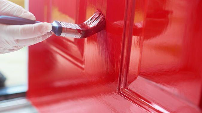 Homeowner gives his front door a new bold lick of paint.