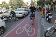 An Iranian man rides a bicyle from bike-sharing service Bdood in the capital Tehran