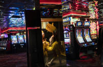 Buskers dressed as showgirls walk into a casino along the Las Vegas Strip in Las Vegas, Feb. 10, 2021. With the ongoing coronavirus pandemic curtailing tourism, visitors have found quiet gambling floors, shuttered showrooms and inexpensive rates. (AP Photo/John Locher)