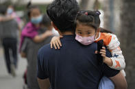 People carry their child wearing face masks to help curb the spread of the coronavirus head to a kindergarten in Beijing on June 9, 2021. If China is to meet its tentative goal of vaccinating 80% of its population against the coronavirus by the end of the year, tens of millions of children may have to start rolling up their sleeves. (AP Photo/Andy Wong)