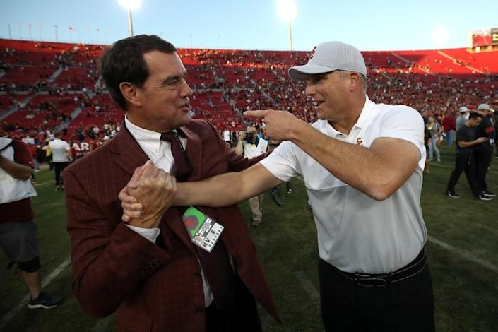 LOS ANGELES, CALIFORNIA - NOVEMBER 23: (L-R) Athletic Director Mike Bohn of the USC Trojans shakes hands with head coach Clay Helton of the USC Trojans after defeating the UCLA Bruins 52-35 in a game at Los Angeles Memorial Coliseum on November 23, 2019 in Los Angeles, California. (Photo by Sean M. Haffey/Getty Images)
