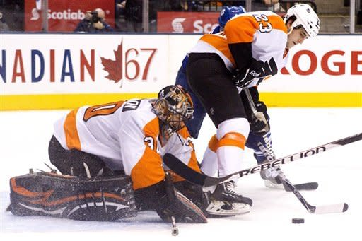 Philadelphia Flyers goaltender Ilya Bryzgalov, left, keeps his eye on a loose puck as Brandon Manning (23) holds off Toronto Maple Leafs' Phil Kessel during the second period of an NHL hockey game in Toronto on Saturday, March 10, 2012. (AP Photo/The Canadian Press, Chris Young)