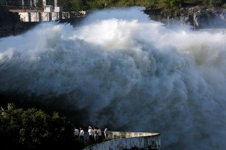 People watch as Hoa Binh hydroelectric power plant opens the flood gates after a heavy rainfall caused by a tropical depression in Hoa Binh province, outside Hanoi, Vietnam October 12, 2017. REUTERS/Kham