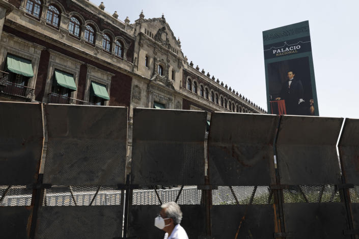 People walk past a perimeter fence set up in front of the National Palace in preparation for the upcoming International Women's Day demonstration, in Mexico City, Friday, March 5, 2021. The colonial-era palace is located on the city's vast central plaza, and is where President Andrés Manuel López Obrador lives and works. (AP Photo/Eduardo Verdugo)