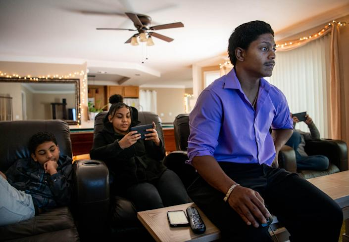 Kendrick Harrison pores over dozens of email exchanges with Argosy University, a for-profit college that was later shut down. Kendrick's children, Alex, far left, 14, and Sierra, 18, are seated behind him at his home in Las Vegas.