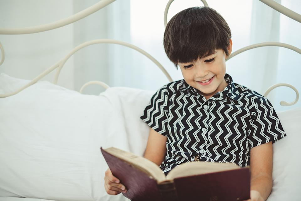 Boy reading book with smile and happy.