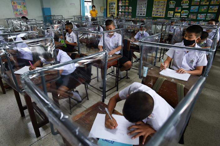 Students sit at desks with plastic sheet shields during the first day of school after the Thai government eased isolation measures and introduced social distancing to prevent the spread of the coronavirus at Watpichai school in Bangkok on July 1.