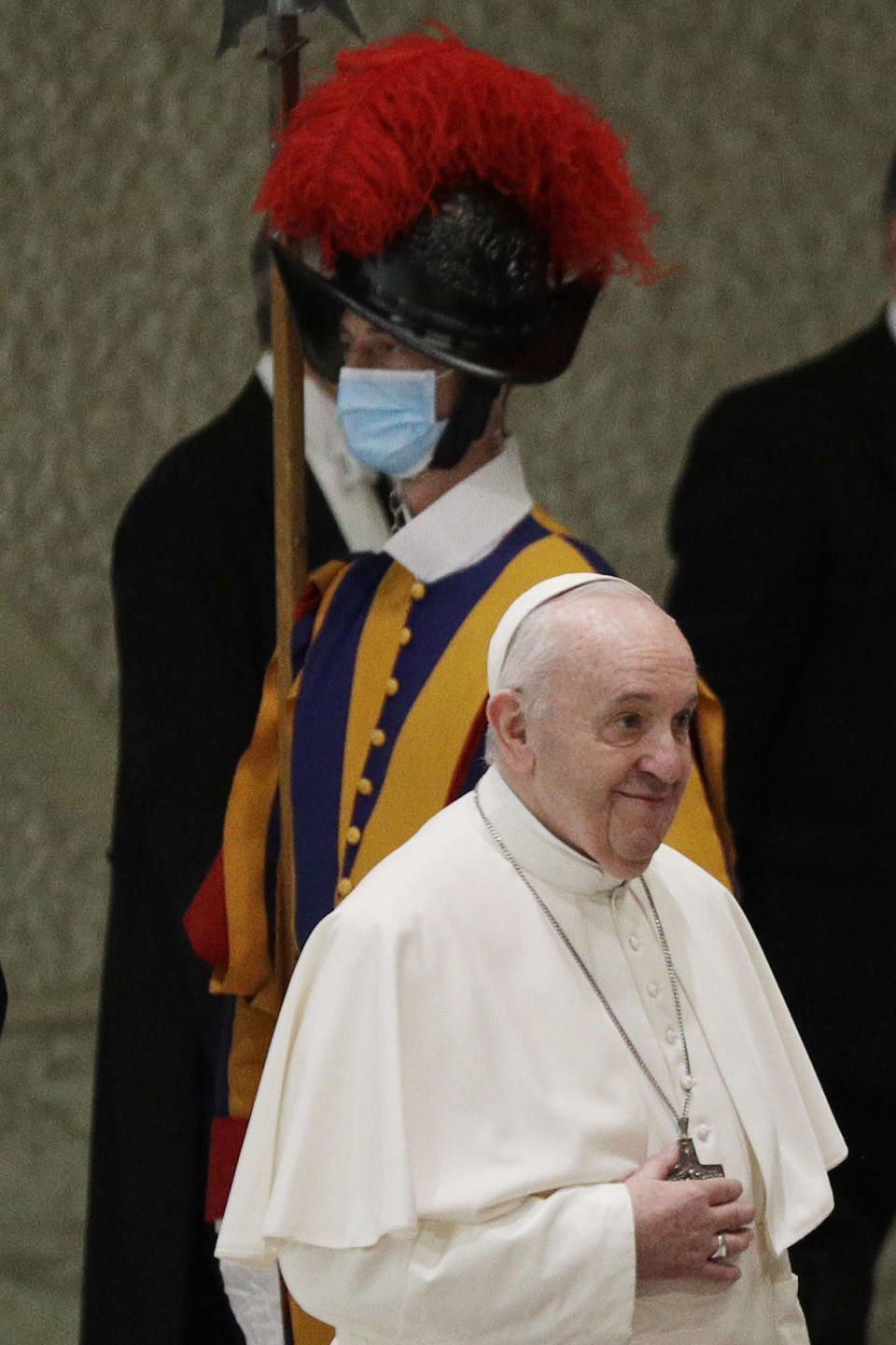 Pope Francis passes by a Swiss guard wearing a face mask to curb the spread of COVID-19 as he arrives in the Paul VI hall on the occasion of the weekly general audience at the Vatican, Wednesday, Oct. 21, 2020. (AP Photo/Gregorio Borgia)