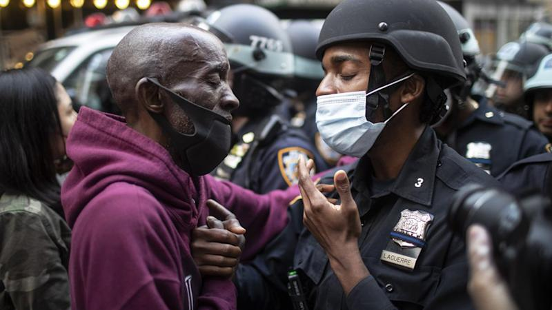 A protester and a police officer shake hands in the middle of a standoff during a solidarity rally