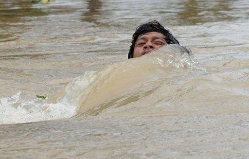 A man is nearly submerged as he crosses a flooded street using a rope in the aftermath of Typhoon Nalgae in Calumpit. The Philippines deployed helicopters, inflatable boats and amphibious vehicles Sunday in a desperate bid to evacuate tens of thousands in the aftermath of successive monster storms